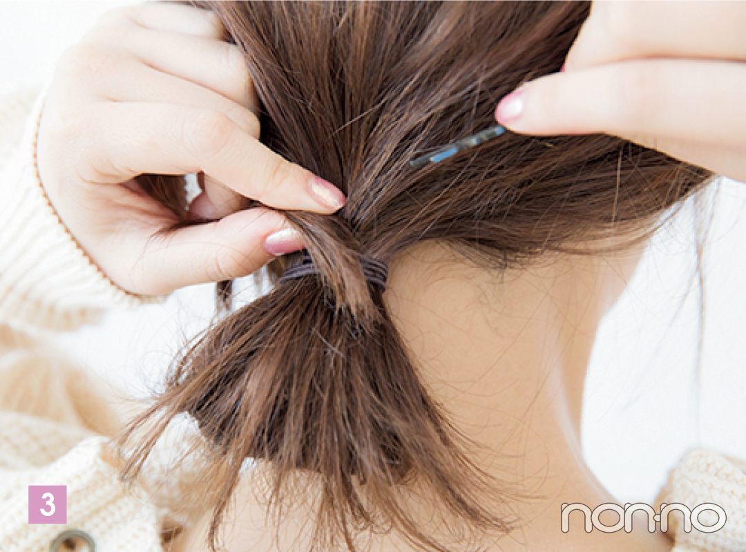 結び目から出ている毛先をゴムに沿って巻きつけ、ピンで固定したら出来上がり。