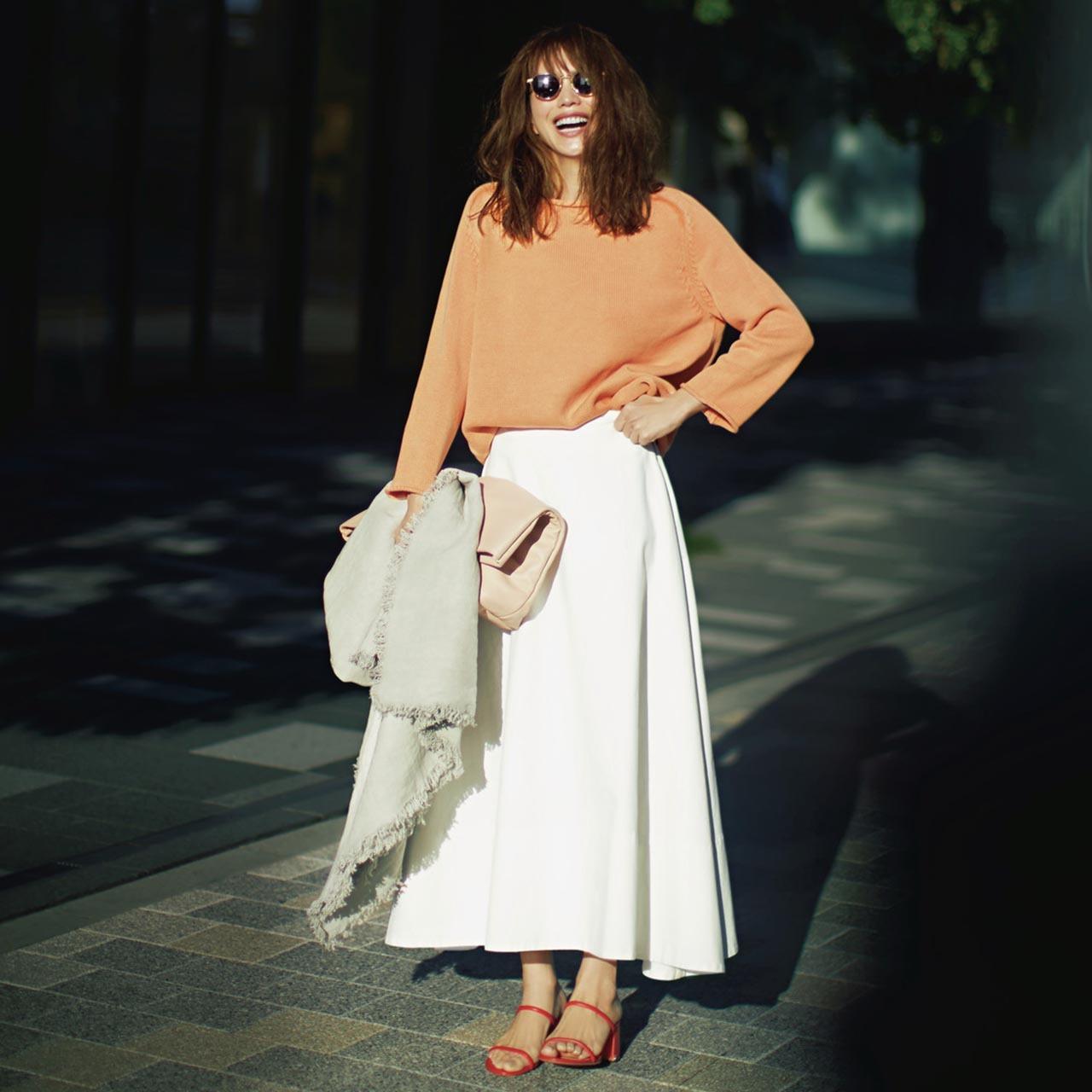 オレンジのニット活ける白のスカートコーデを着たモデルの蛯原友里さん