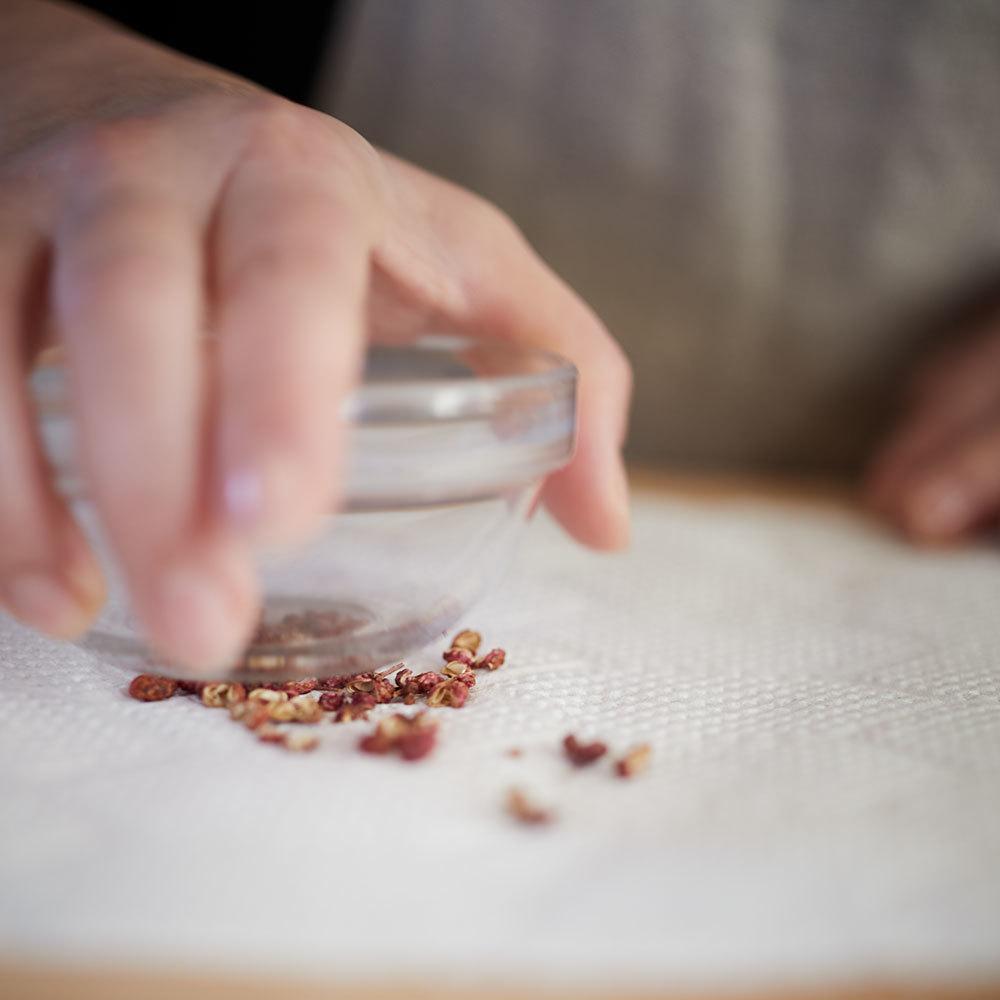 花椒をつぶすときは耐熱の小ボウルやデュラレックスなどの厚手のグラス、瓶詰などの底で。好みの粗さまでつぶす
