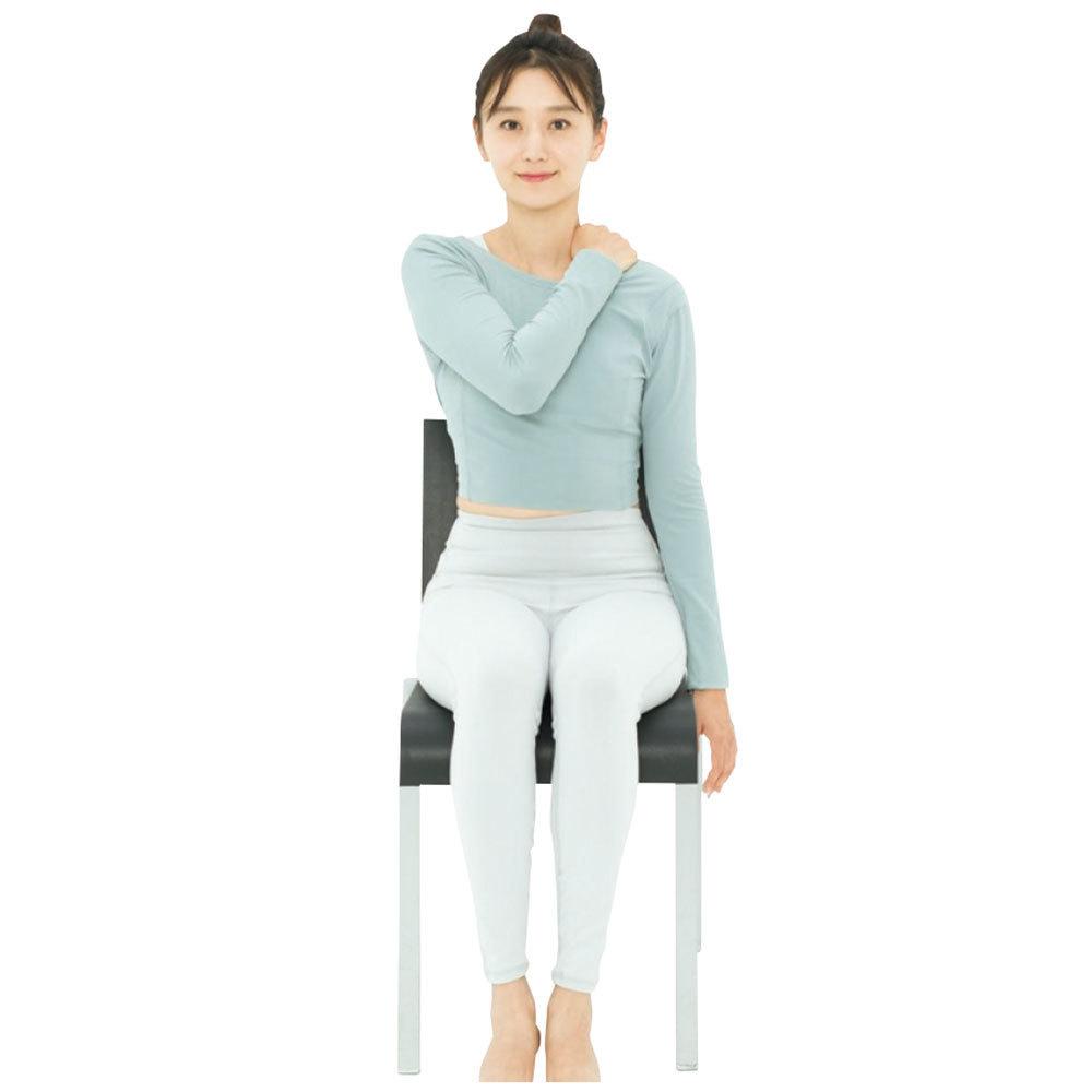背中握手をしやすくするのに効果的な方法。椅子に座り、右手で左肩をつかむ。
