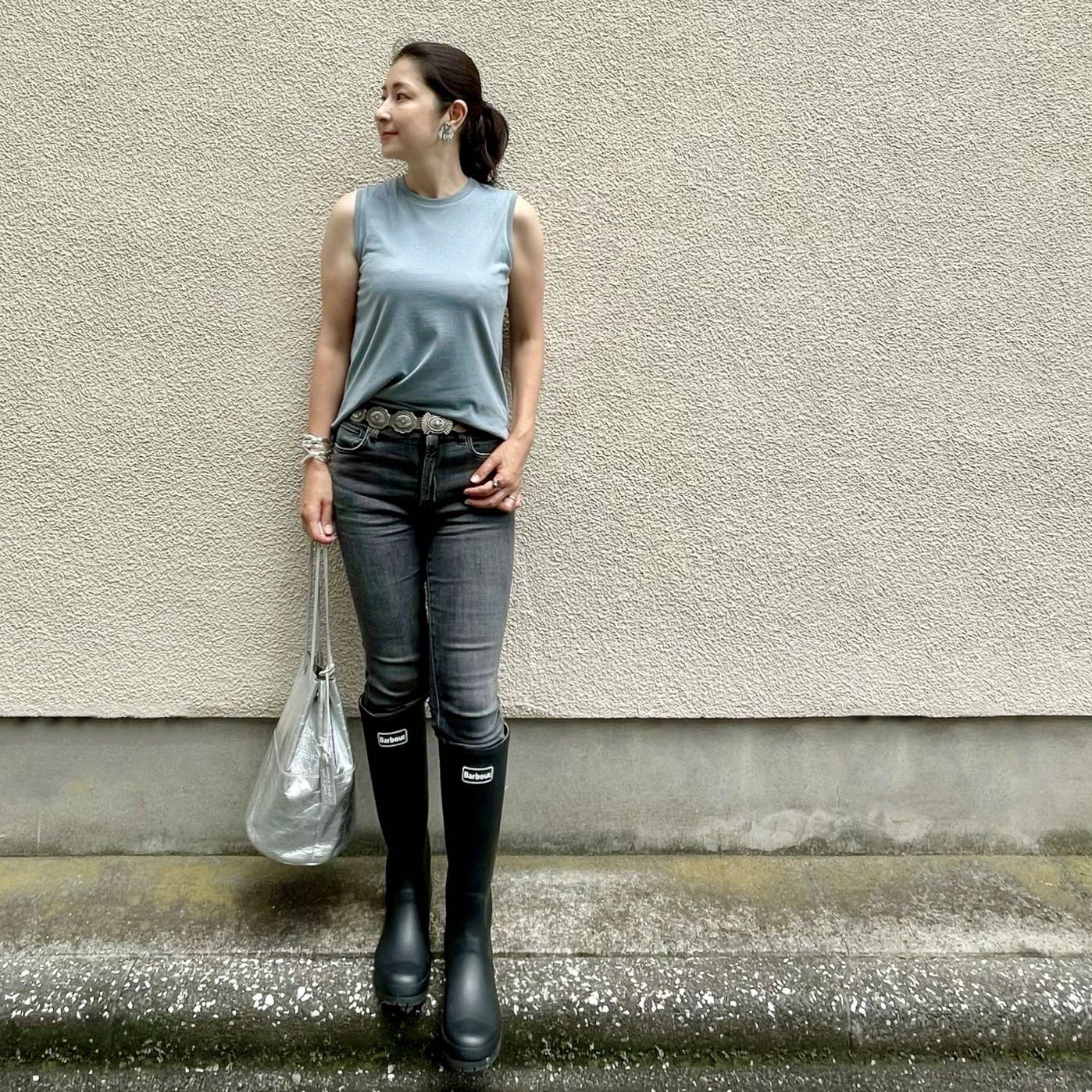 くるみブルーのノースリーブTシャツ、黒デニム、黒のレインブーツ、シルバーのバッグ、コンチョベルト