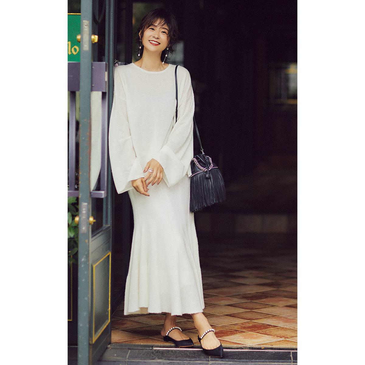 白のニット×フレアスカートのセットアップコーデを着たモデルの五明祐子さん