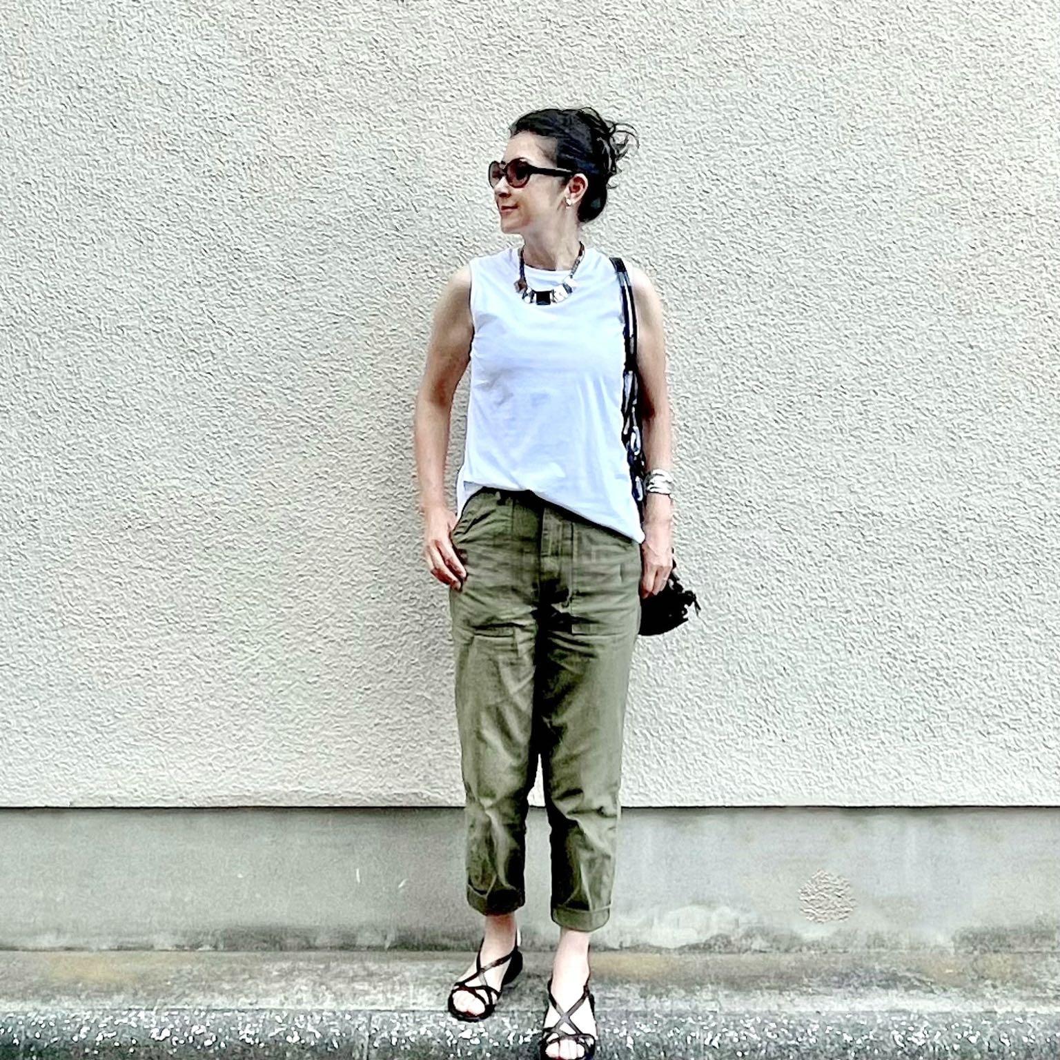 ユニクロの白のノースリーブTシャツ、カーキのベイカーパンツ、ブラックのフラットサンダル、ブラックのメッシュバッグ、大振りのショートネックレス