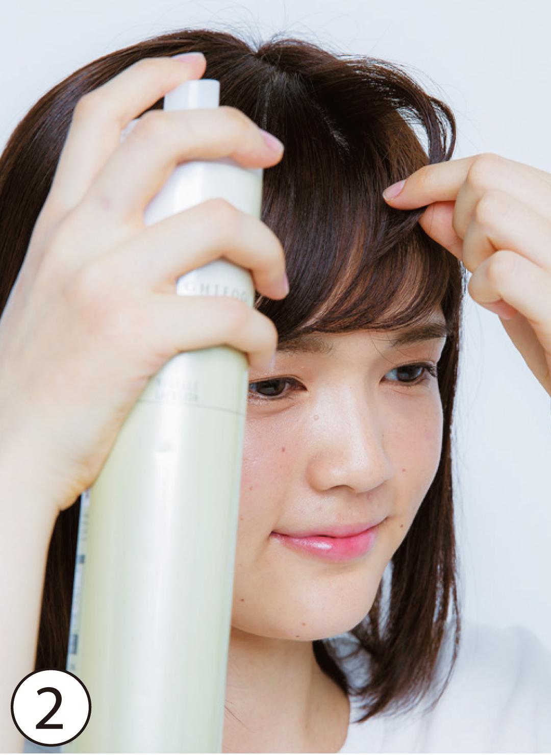②スプレーを使って前髪表面に立体感 基本のスタイリング④の後、前髪表面の毛束を少し取ってスプレーで浮かせる。立体感を作ることで、顔の横幅をカバー。