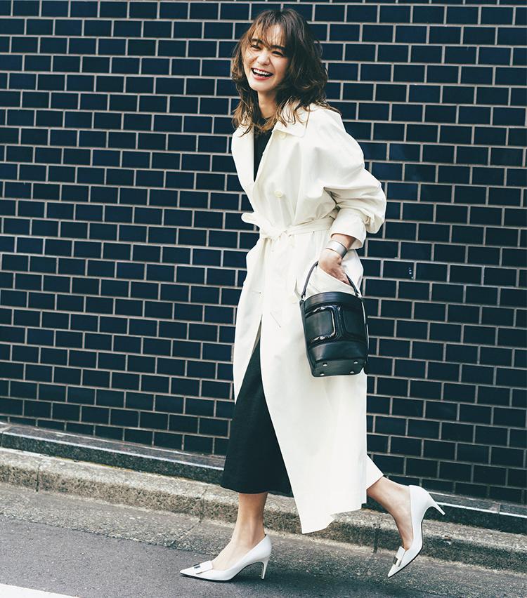 白のトレンチコート×黒のスカートコーデを着たモデルの竹下玲奈さん