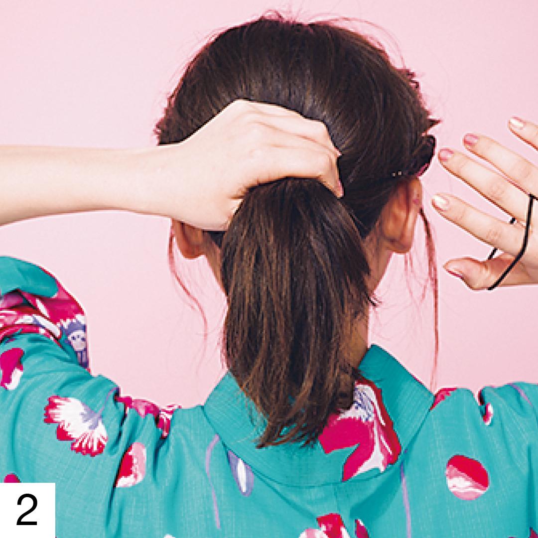 左も同様にねじったら、ねじった髪もすべて手ぐしでざっくりまとめて、耳の位置くらいの低めのポニーテールにする。毛束を少し取り、結び目に巻きつけてゴムを隠す。