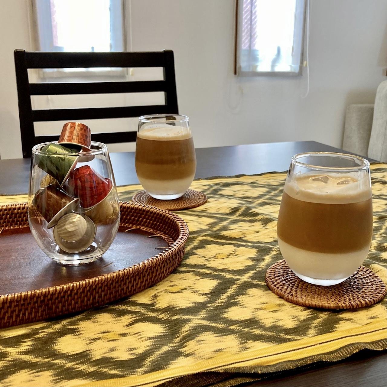 ダイニングテーブルに黄色のテーブルランナーとアイスコーヒー