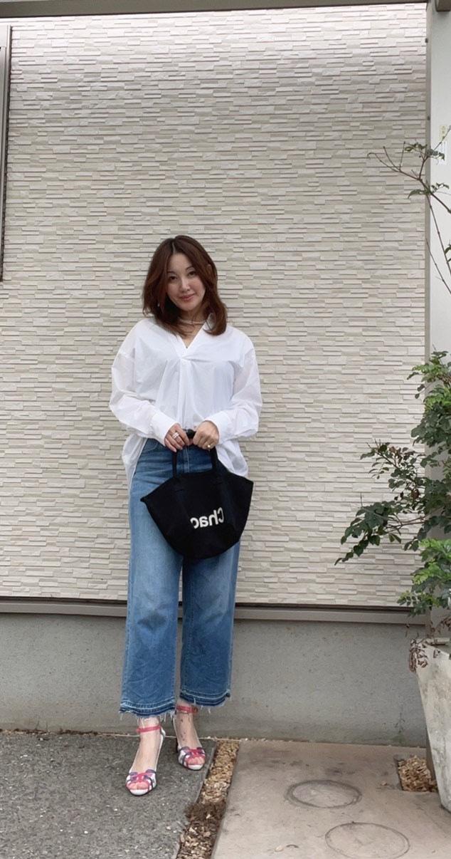白い壁の前 ジーンズ、白シャツ、黒のトートバッグを持った女性