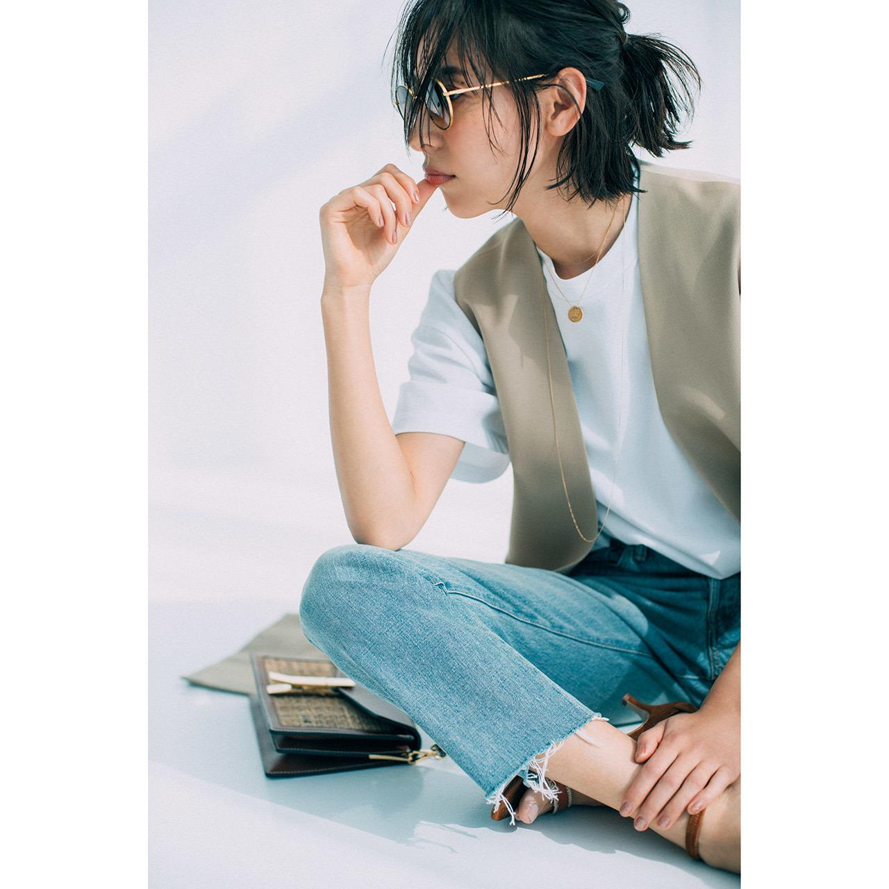 コインネックレス×白Tシャツ×ベスト×デニムパンツコーデを着たモデルの小泉里子さん