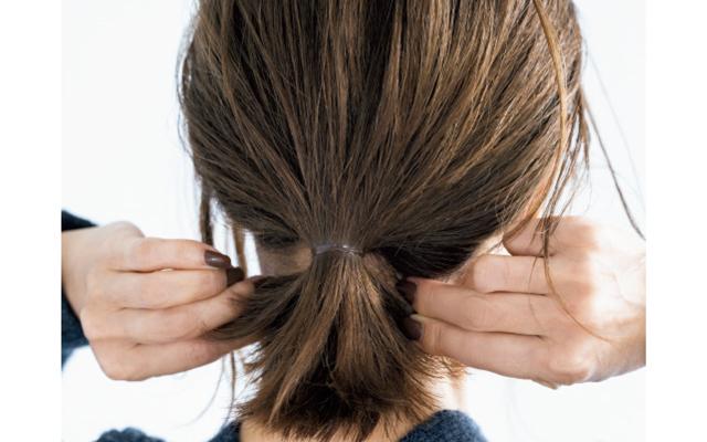 毛束の内側を引っぱり広げると、結んだ部分が襟足に添う