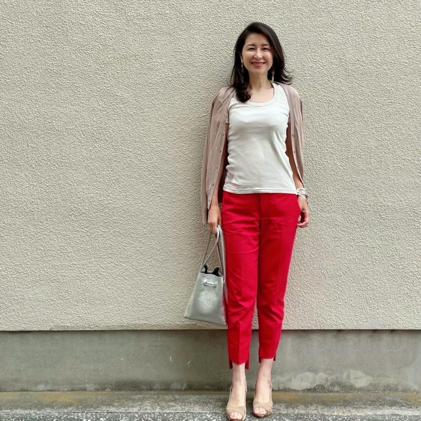 赤のクロップドパンツ、ライトベージュのTシャツ、ベージュのカーディガン、ベージュのサンダル、シルバーバッグ