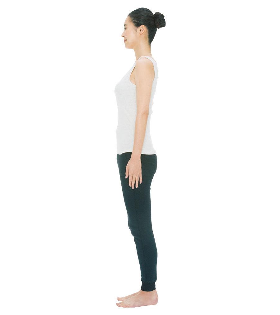 足を肩幅程度に開いて立ち、顔を正面に向けて軽くあごを引き、目線を下げる。首の後ろ側の伸びを感じて。