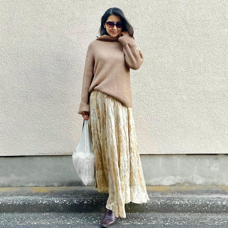 ベージュのローゲージニット、ゴールドの花柄スカート、白のファーバッグ、茶のロングブーツ