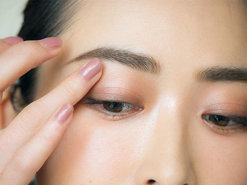 ①モーヴブラウンのクリームシャドウを指で塗る。目のくぼみが目立つ人  はアイホールまで、目立たない人はもっと上まで