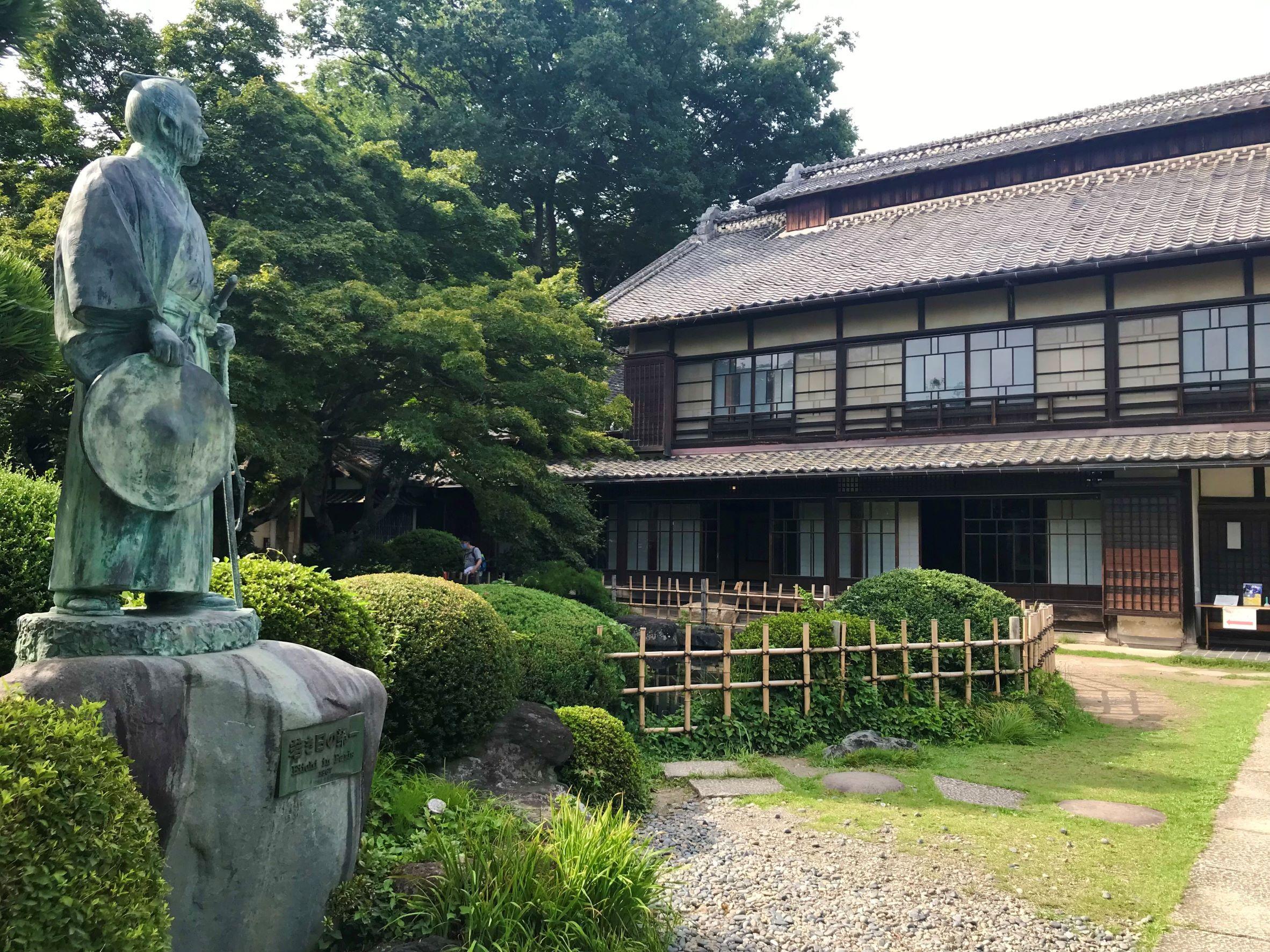 「若き日の栄一」像と主屋/中の家