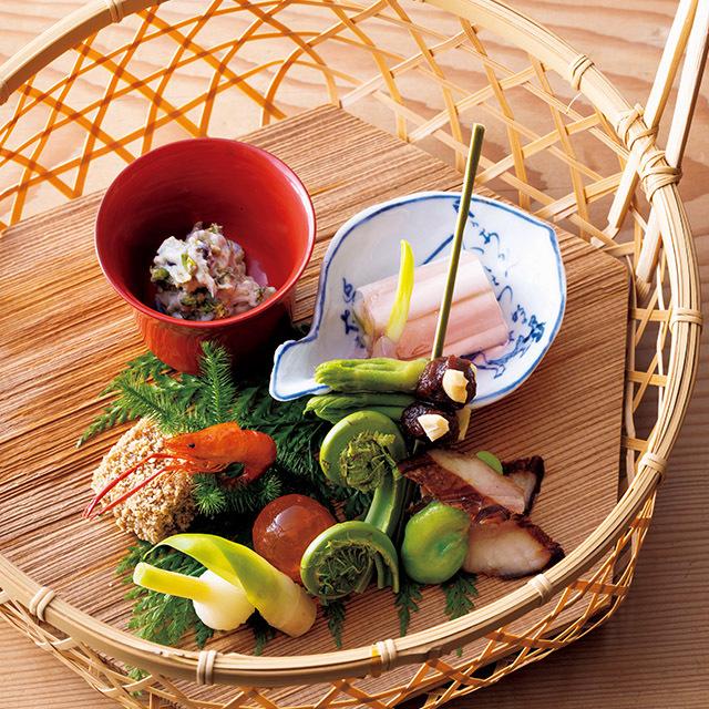 ふきのとう白あえ、うるい甘酢ゼリー寄せ、タラの芽田楽、のびる甘酢漬けなどを盛った「菜籠」