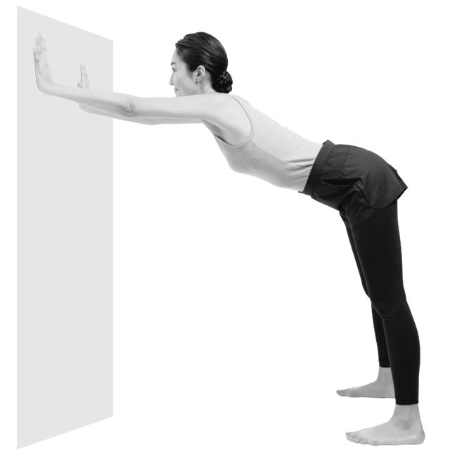 壁から少し離れた位置で、足を腰幅に開いて立つ。顔と同じくらいの高さで、壁に両手をつける