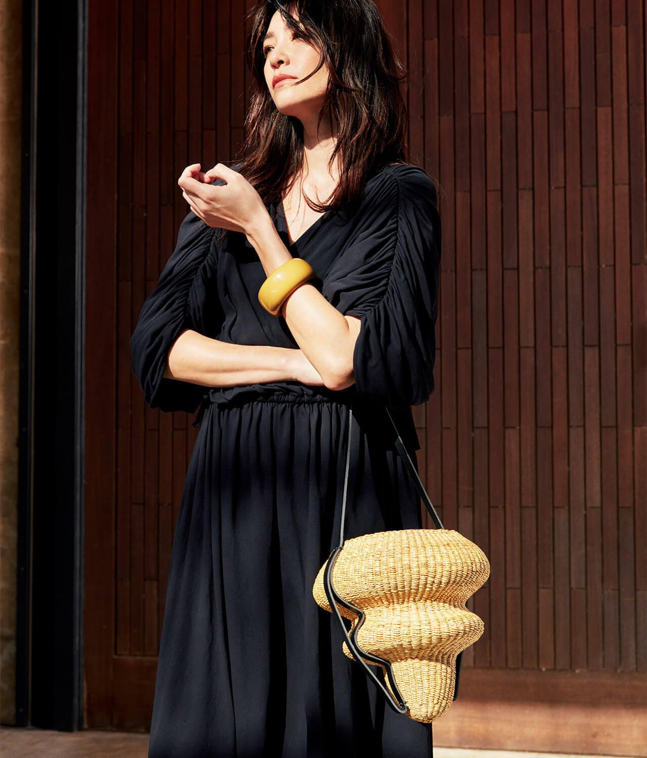黒ワンピースにかごバッグをあわせたコーディネートのモデル・RINAさん