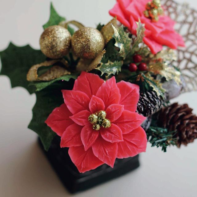 赤い石鹸を彫ったポインセチアを クリスマスアイテムと一緒に黒い器に