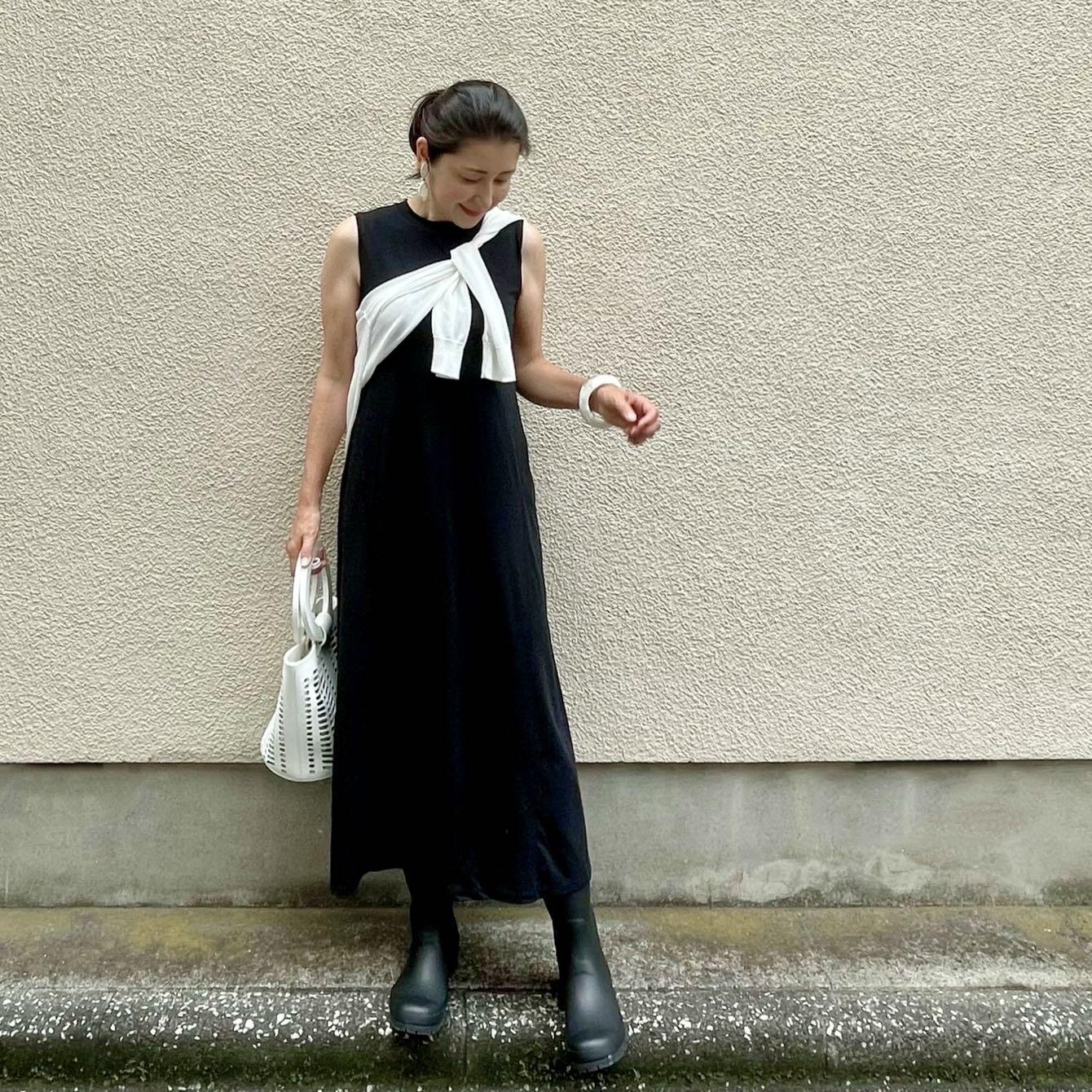 黒のロングワンピース、白のカーディガン、白のバッグ、白のバングル、白のイヤリング、黒のレインブーツ