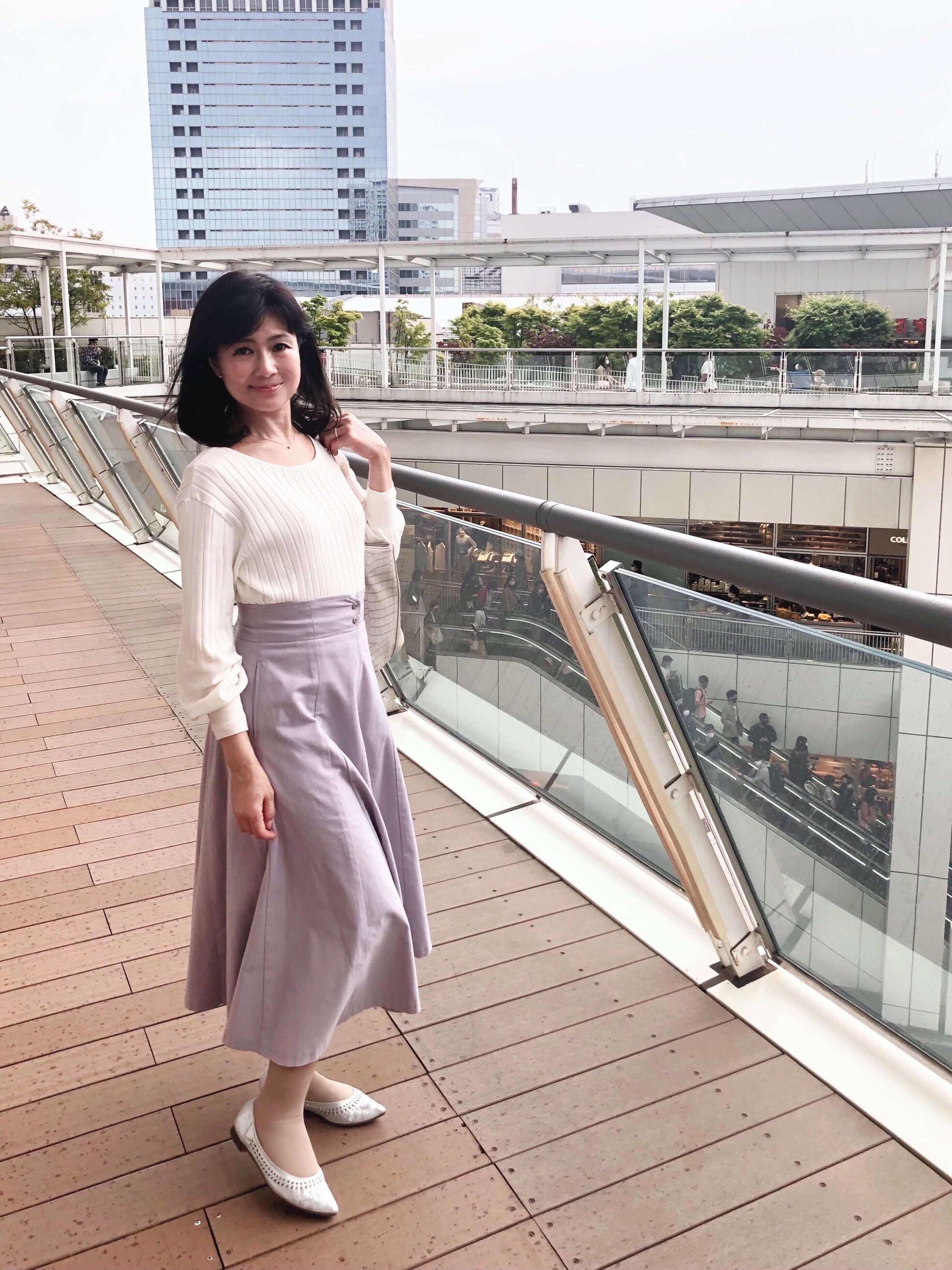 白のトップスに薄紫のロングスカート。シルバーのパンプス。