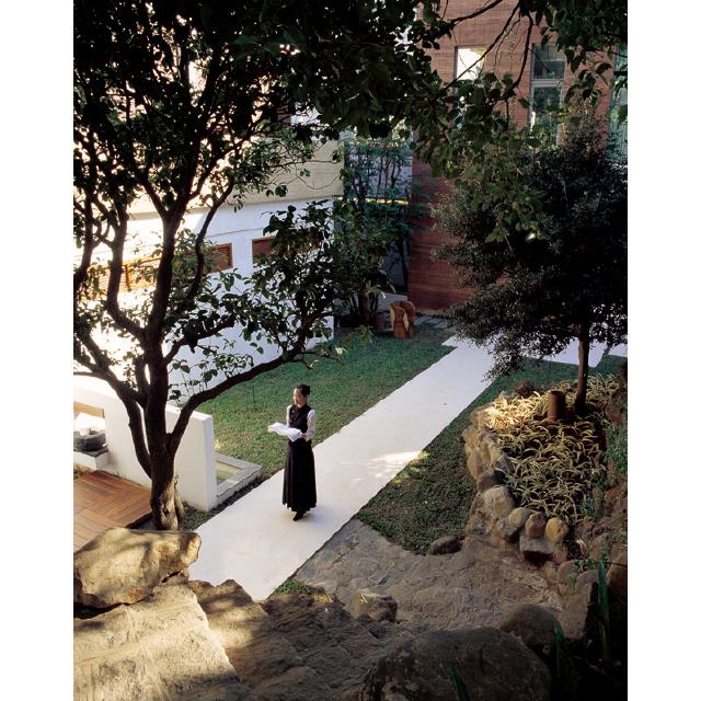 白い道や壁の整然さが調和する中庭