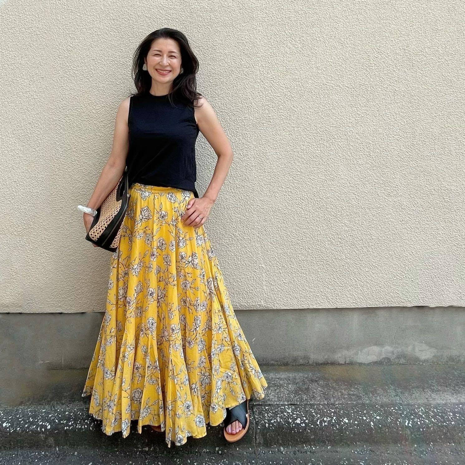 黒ノースリーブTシャツ、イエローの花柄スカート、黒フラットサンダル、黒のレザーとラフィアのバッグ