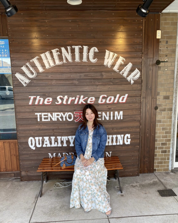 大きな板版看板の前でベンチに座る女性
