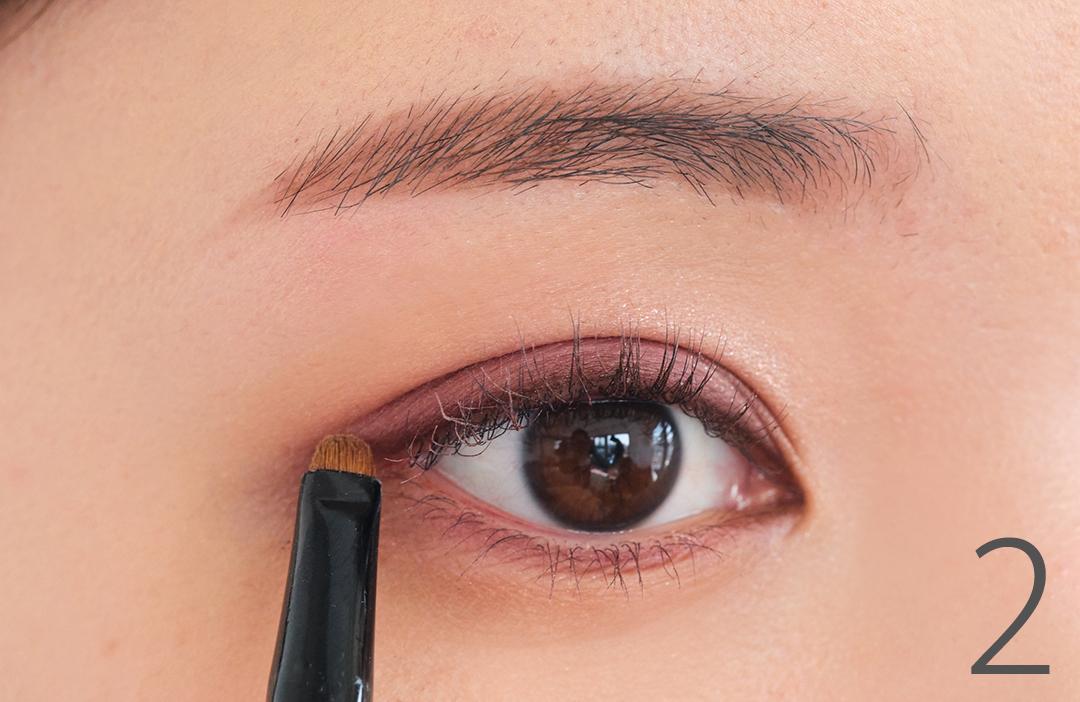 2. Dを小さめのブラシで取り、目のキワにライン状に入れる。目尻は真横に少しだけのばして、優しい色気っぽさを感じさせて。
