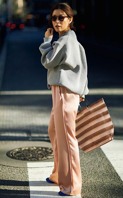 くすみピンクのつや素材パンツ×コンクリートグレーのニットコーデの大草直子さん