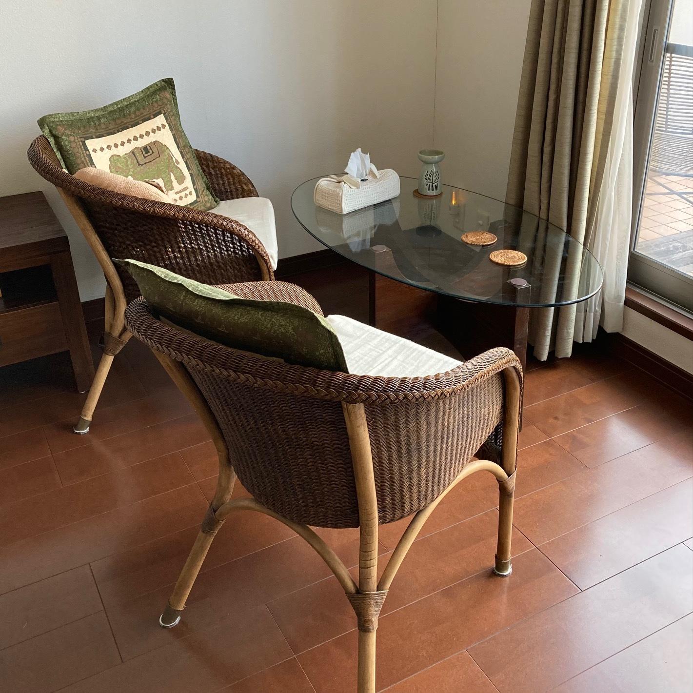 窓に面したコーヒーテーブルと藤の椅子セット