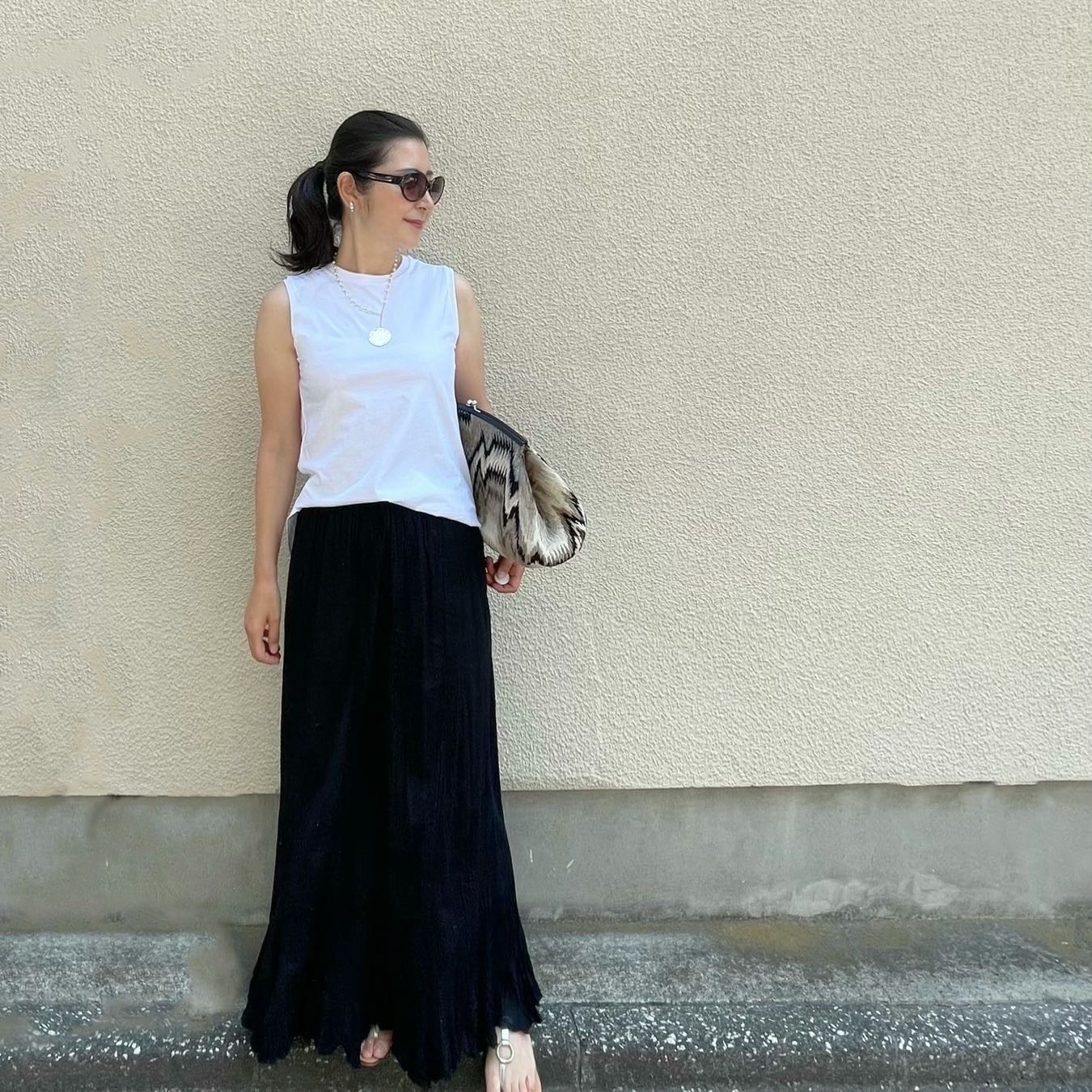 ユニクロの白ノースリーブTシャツ、黒のマキシ丈スカート、大きめのクラッチバッグ、シルバーのフラットサンダル、パールとシルバーの細めネックレス