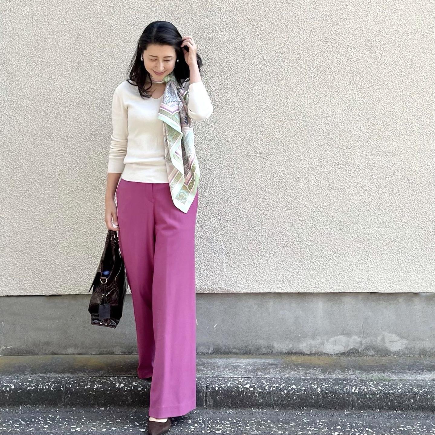 白のVネックニット、ピンクのワイドパンツ、スカーフ、ブラウンのバッグとパンプス