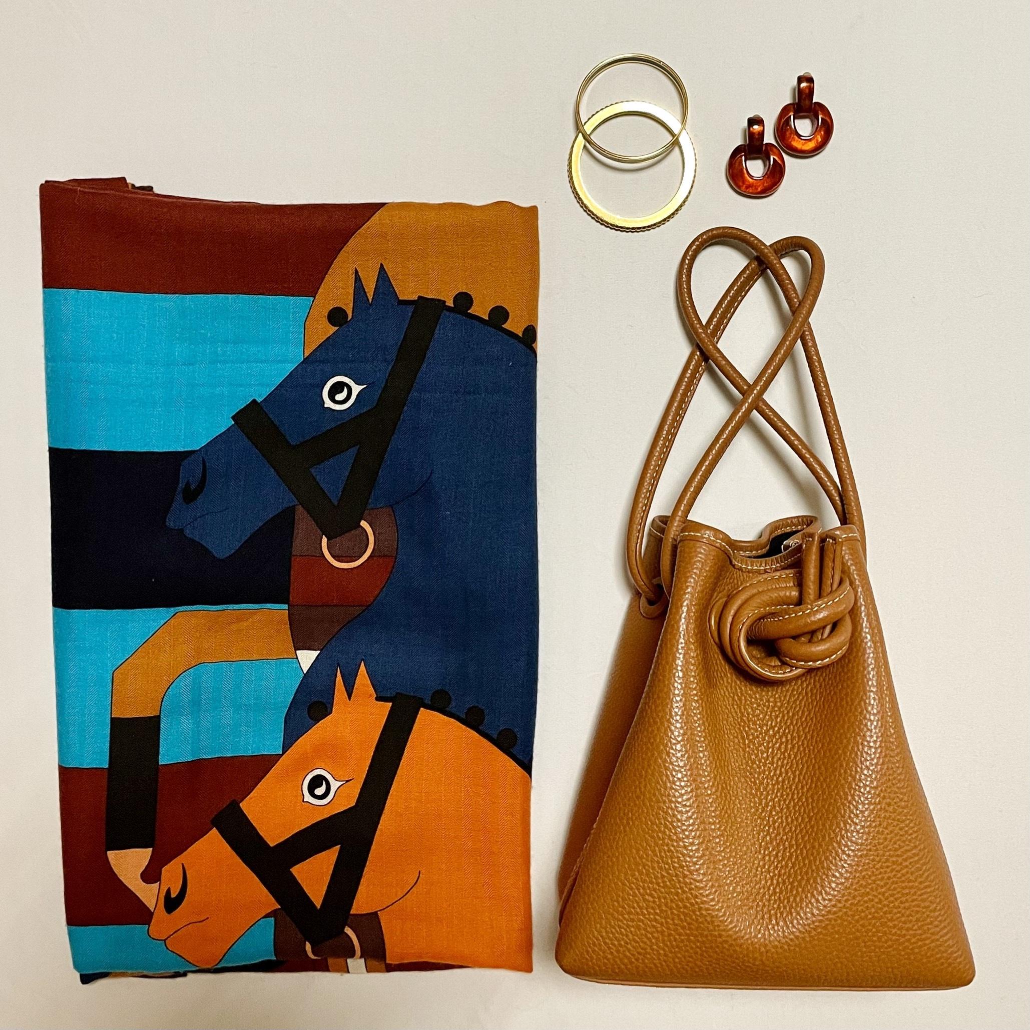 スカーフ柄の大きめストール、キャメルのバッグ、ゴールドの細めバングル、オレンジのイヤリング