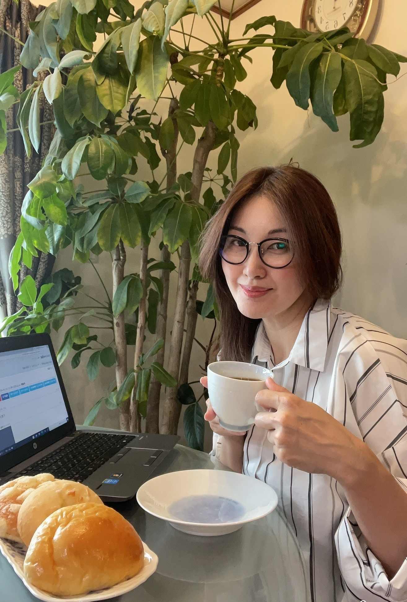 パソコン前 コーヒーカップを持つ女性