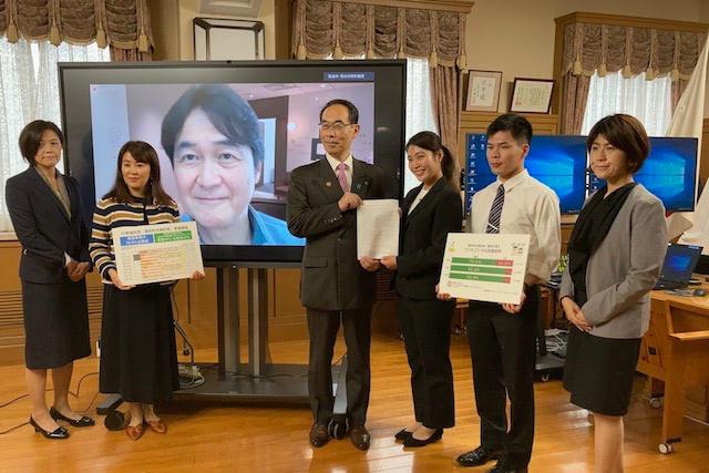 5月13日、埼玉県知事に法改正の要望を手渡した。プロジェクターに映るのは、ビジネスリーダー有志の会共同代表を務めるドワンゴの夏野剛社長