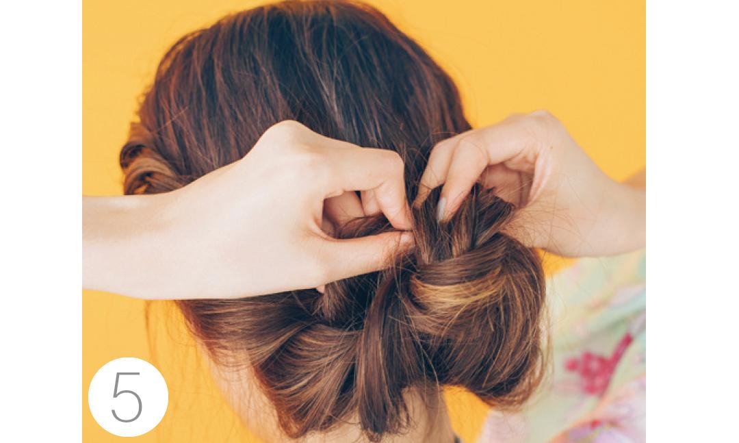 毛束を下から上に持ち上げながらくるくるとまとめる。ピンでしっかり固定して。最後に髪飾りを。
