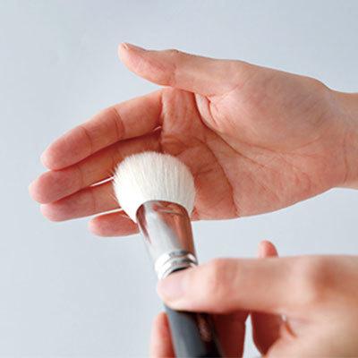 化粧ブラシの汚れを手で拭き取る