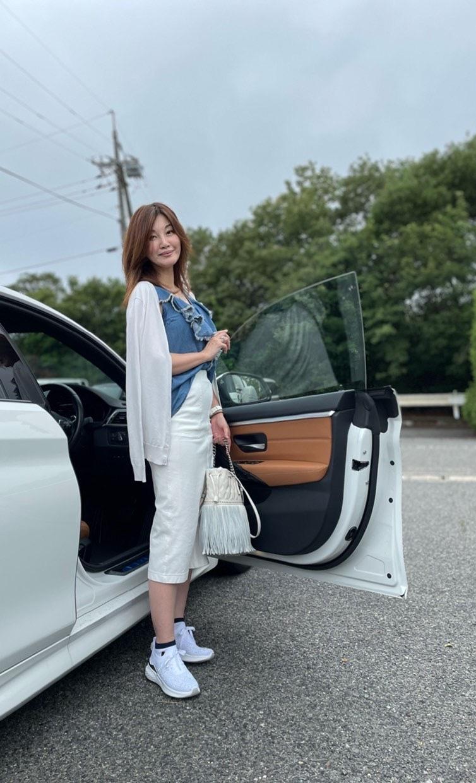 白い車の前に立つ女性