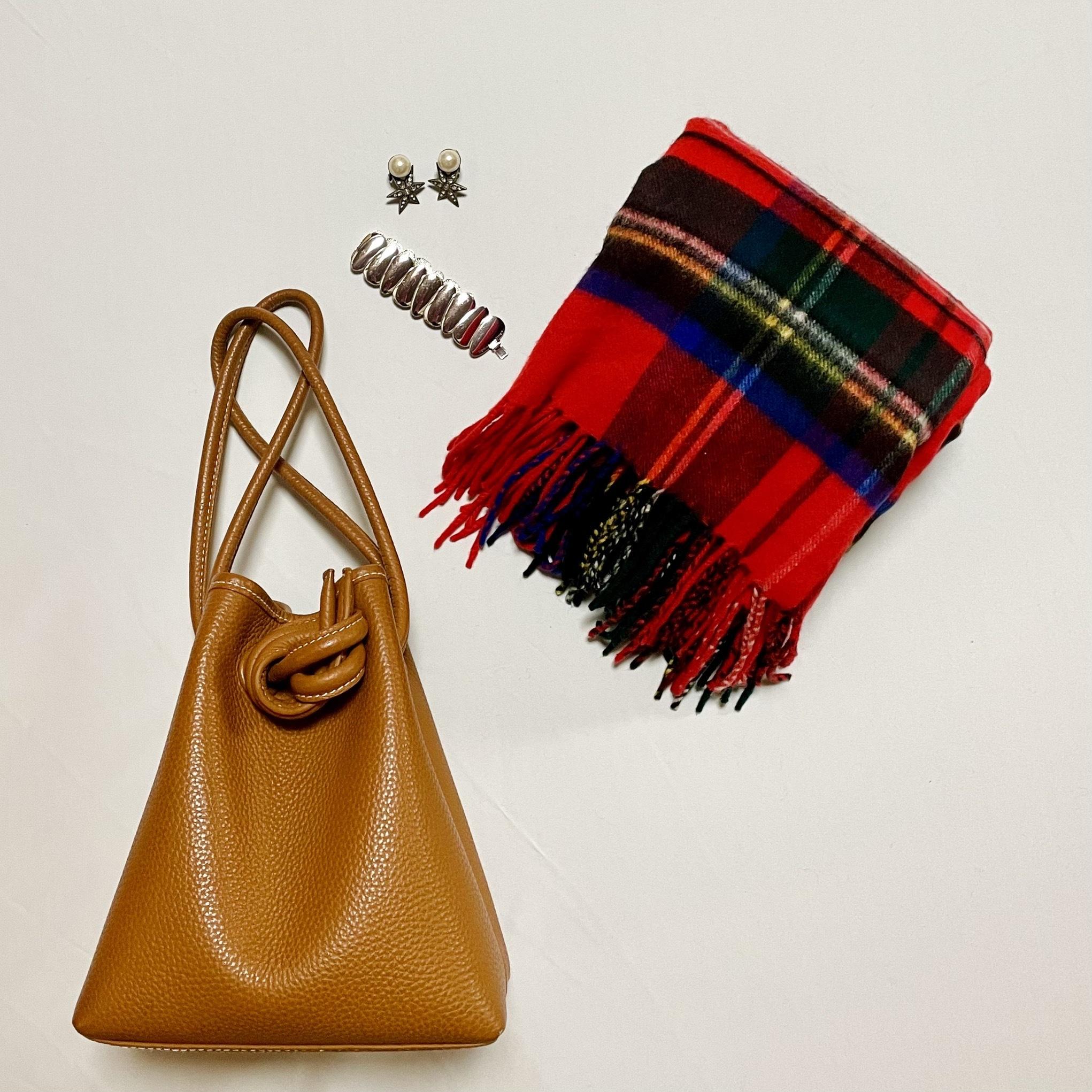 キャメルのバッグ、赤いチェックの大判ストール、パールと星形を組み合わせたイヤリング、シルバーの太めブレスレット