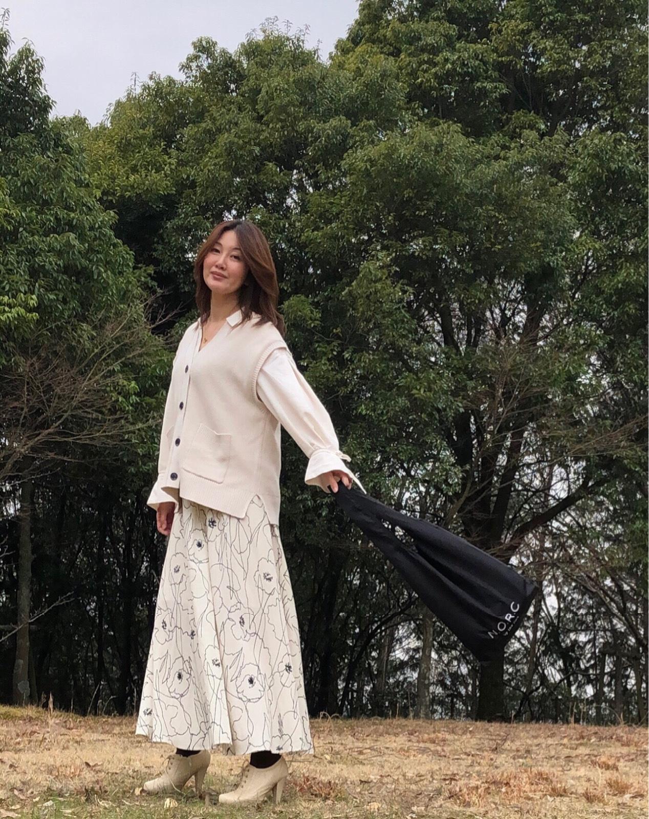 白色ブラウス 白色ニットベスト 白地に黒の模様ロングスカート ショッパーバッグを持って立つ女性 斜めの姿