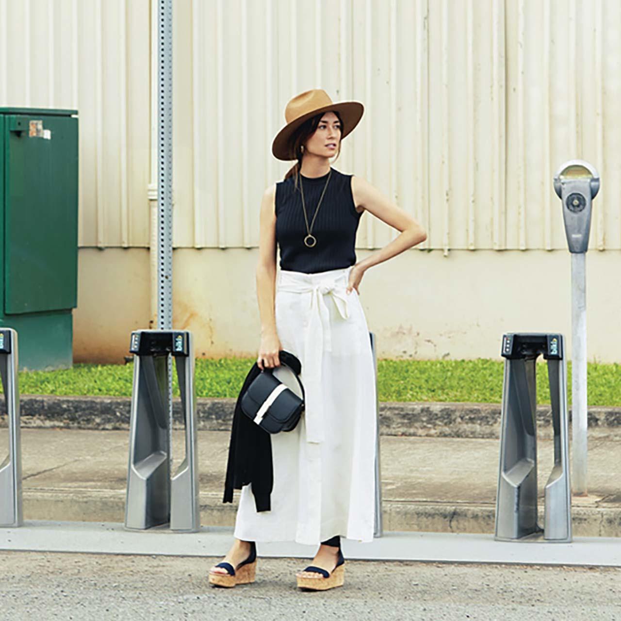 ノースリーブニット×リボンつき白スカートコーデを着たモデルのブレンダさん