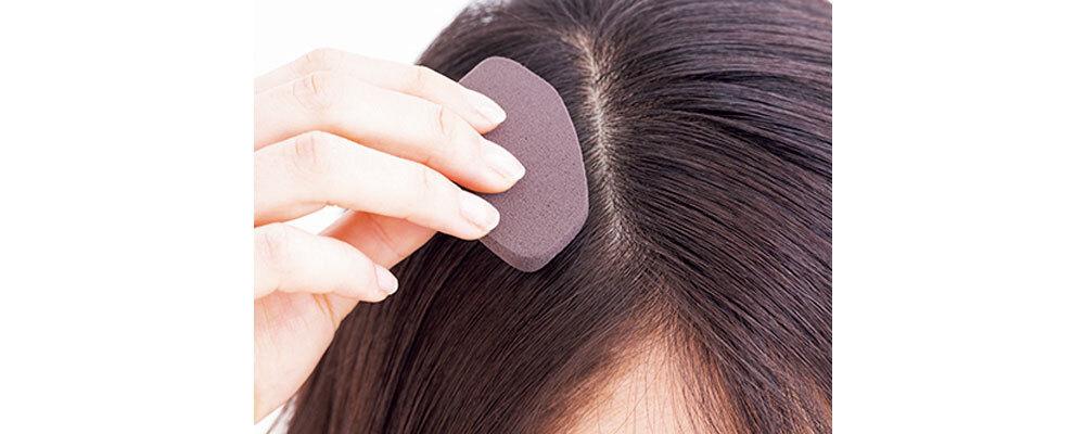 ファンデーションをつけたスポンジを頭頂部の髪の生え際に当てている様子
