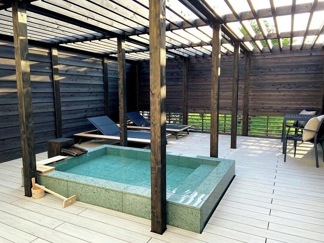 広いテラスには、源泉掛け流しの温泉露天風呂を備える。