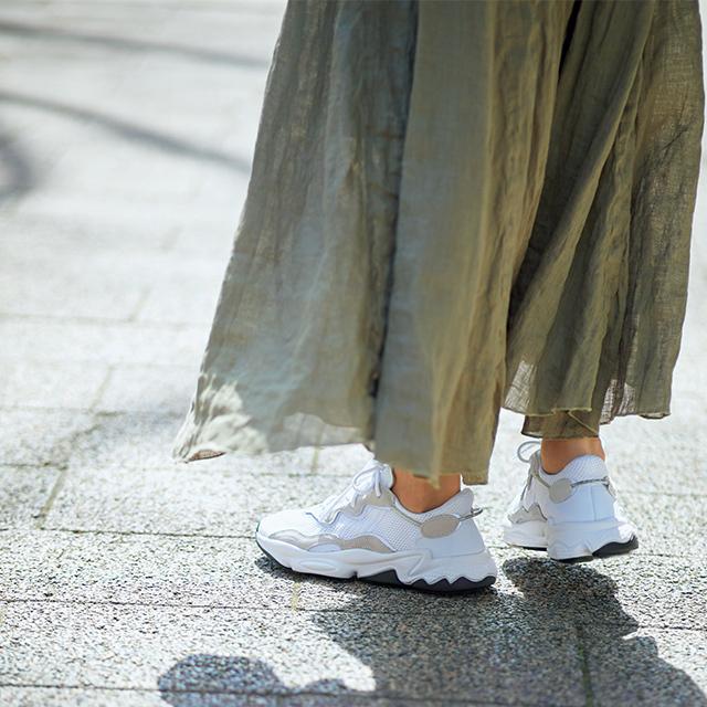 カーキスカートとスニーカーにあしらった淡いグレージュが好相性。
