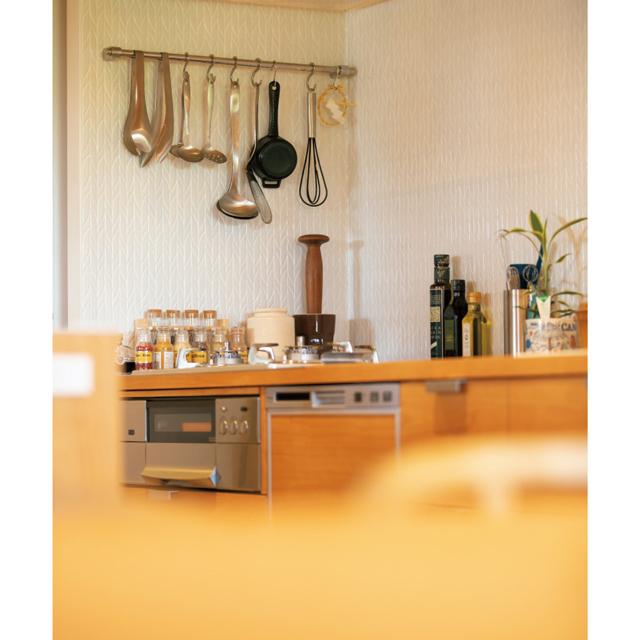 キッチンの収納部分はカバ材、天板はステンレス、壁は表情のあるタイルを選んだ
