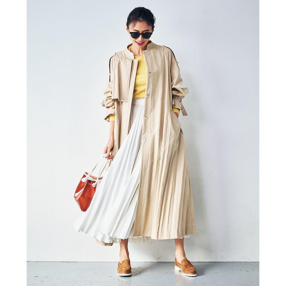 ベージュのトレンチコート×イエローニット&白プリーツスカートのファッションコーデ