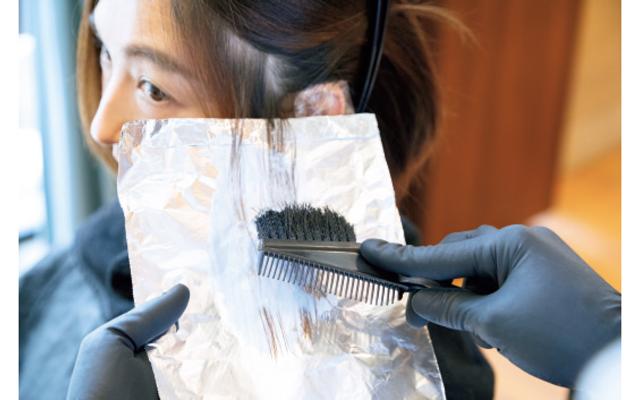 色を抜く耳まわりの部分だけ毛束を太めにとり、ケアブリーチで色を抜く