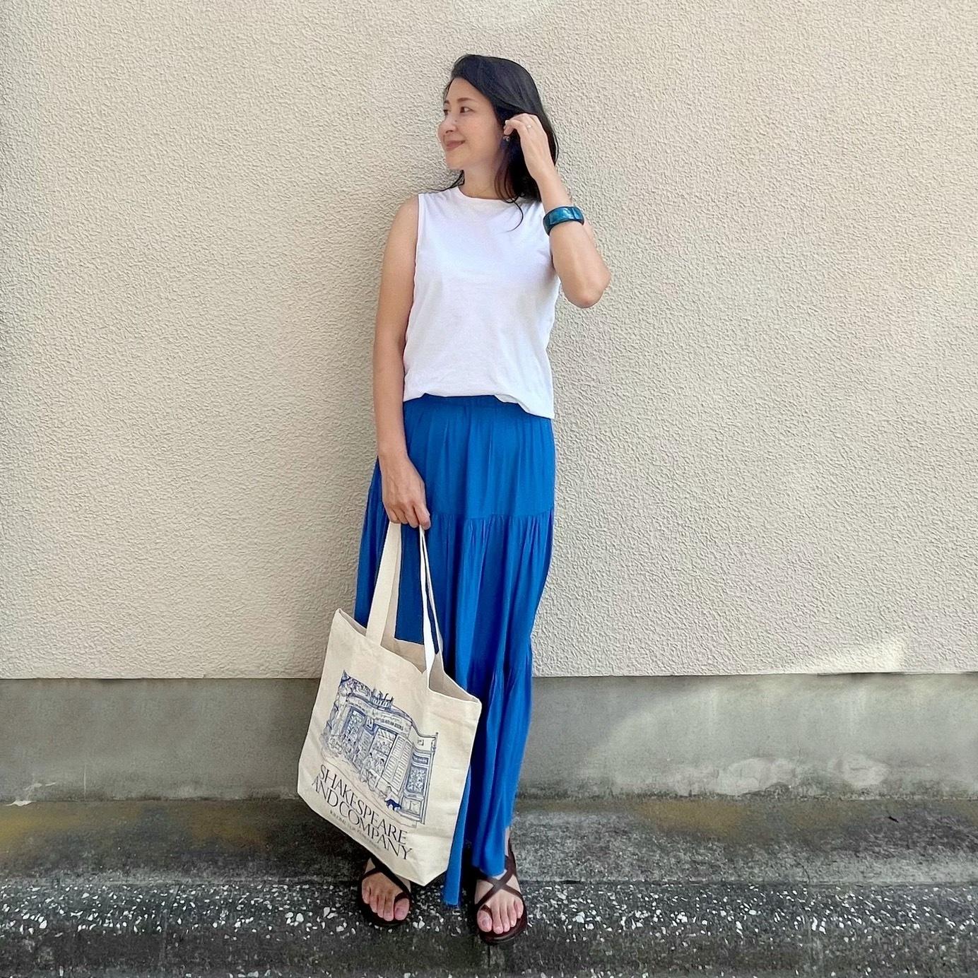 白Tシャツ、ブルーのマキシ丈スカート、ブラウンサンダル、エコバッグ