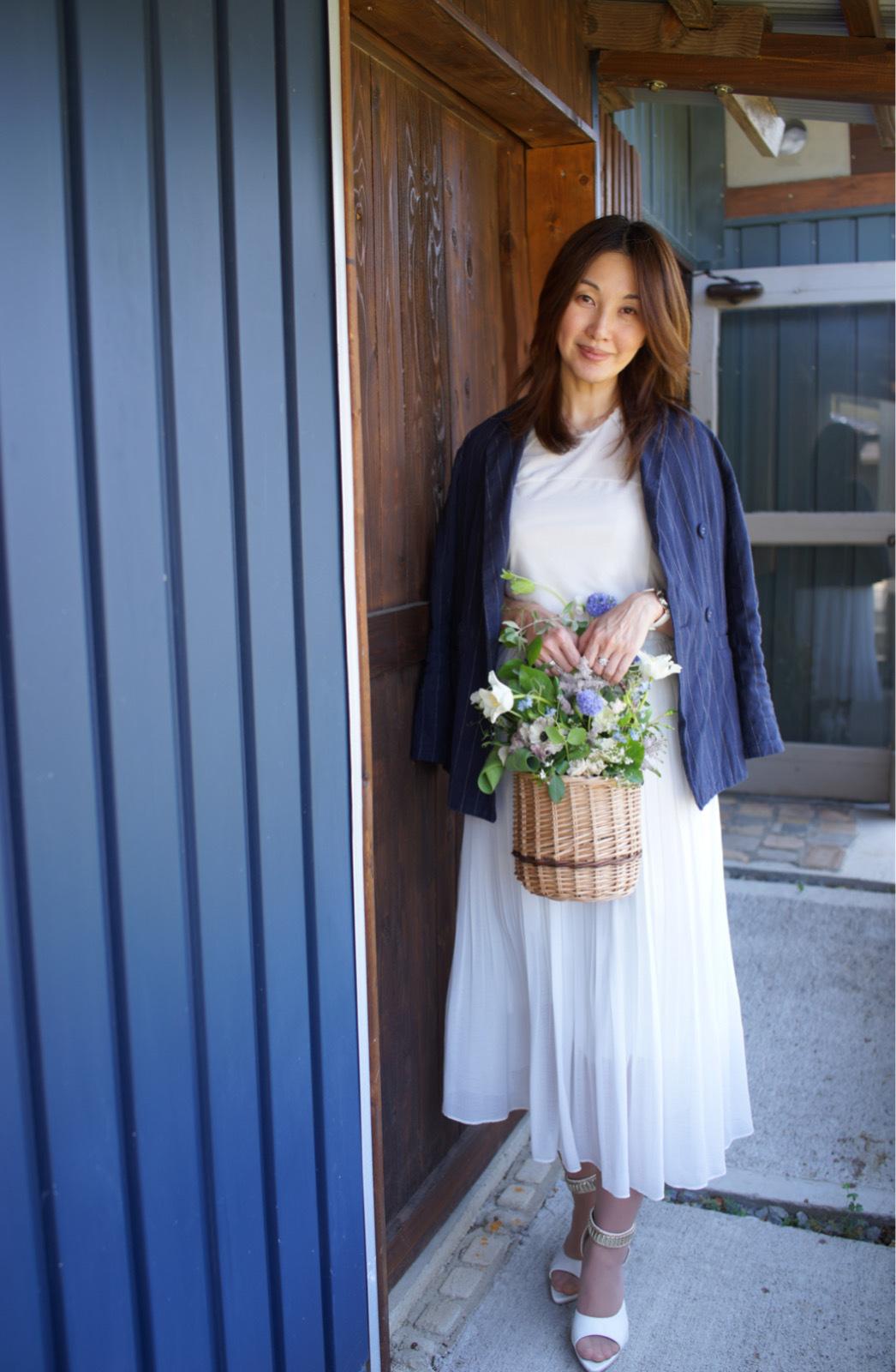 紺色Wジャケット 白カットソーと白プリーツスカート 花バスケットアレンジメントを持った女性